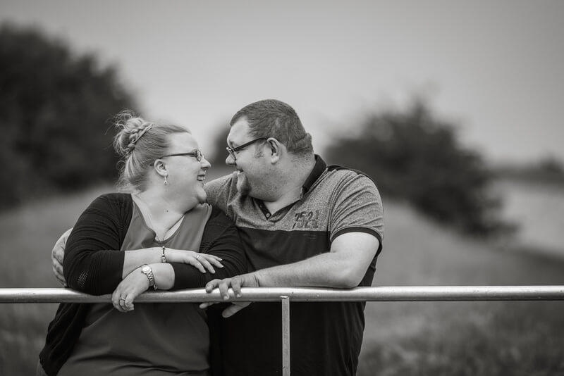 Slice of Life Photography - Relaxed engagement photo leaning against a gate, pre-wedding photo by Cambridgeshire wedding photographer