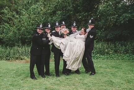 Bride being held up by policemen