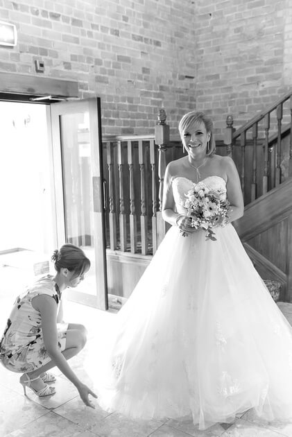 Slice of Life Photography - Bridesmaid adjusts the dress prior to the ceremony, Kings Lynn wedding photographer
