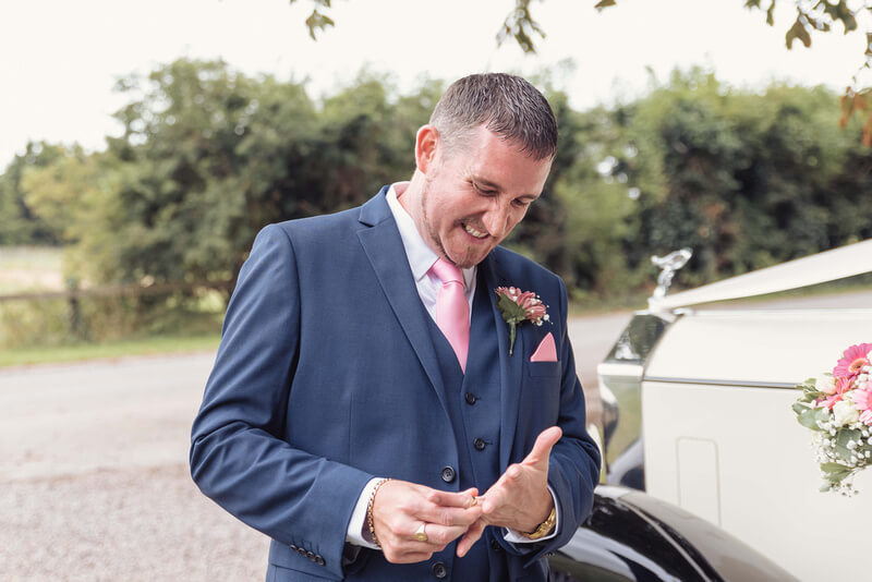 Slice of Life Photography - fun photo of groom trying to remove his wedding ring, Peterborough wedding photographer
