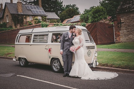 bride and groom standing next to a campervan