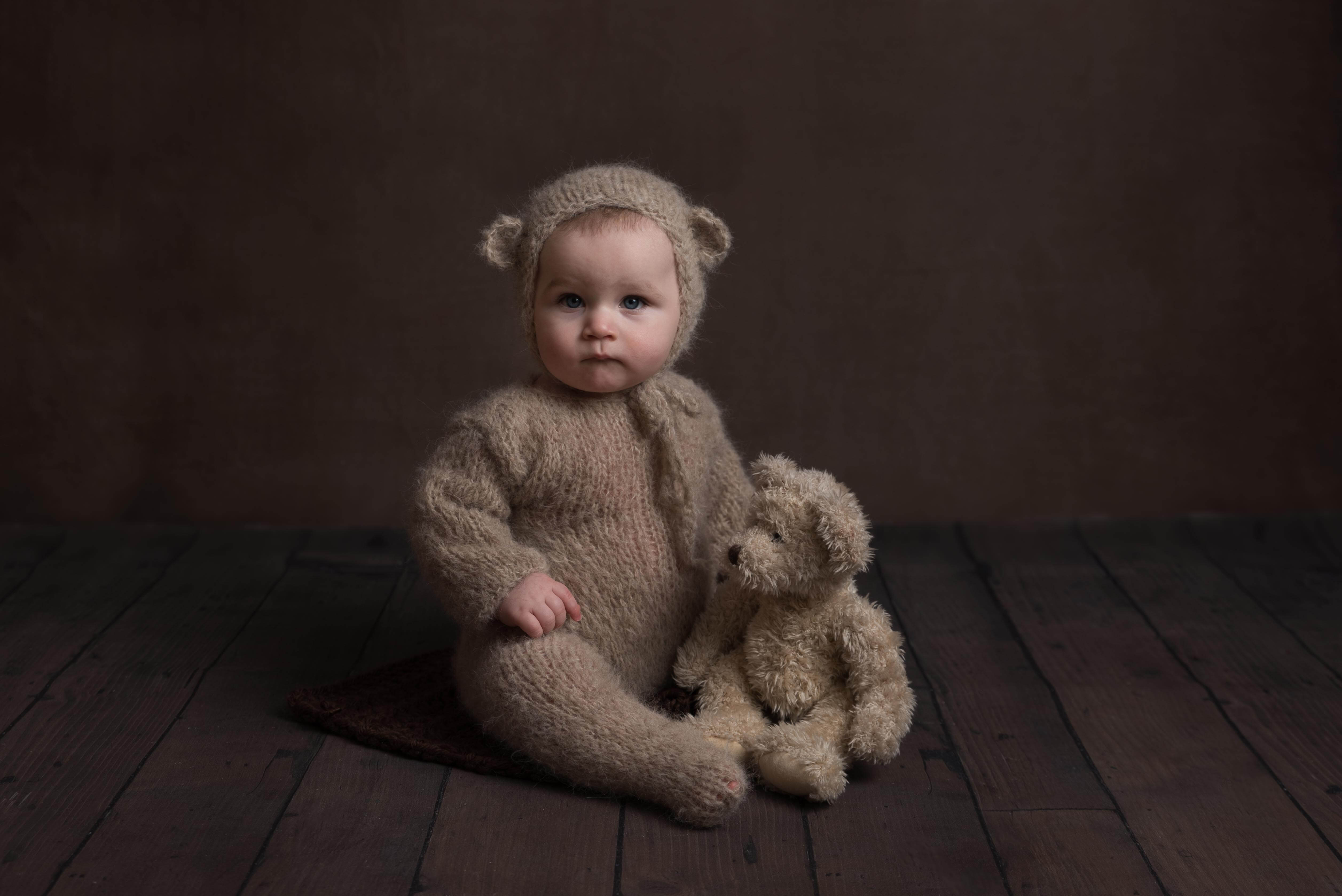 Slice of Life Little Sitters Session Gallery - Baby wearing a teddy bear onesie holding a teddy bear