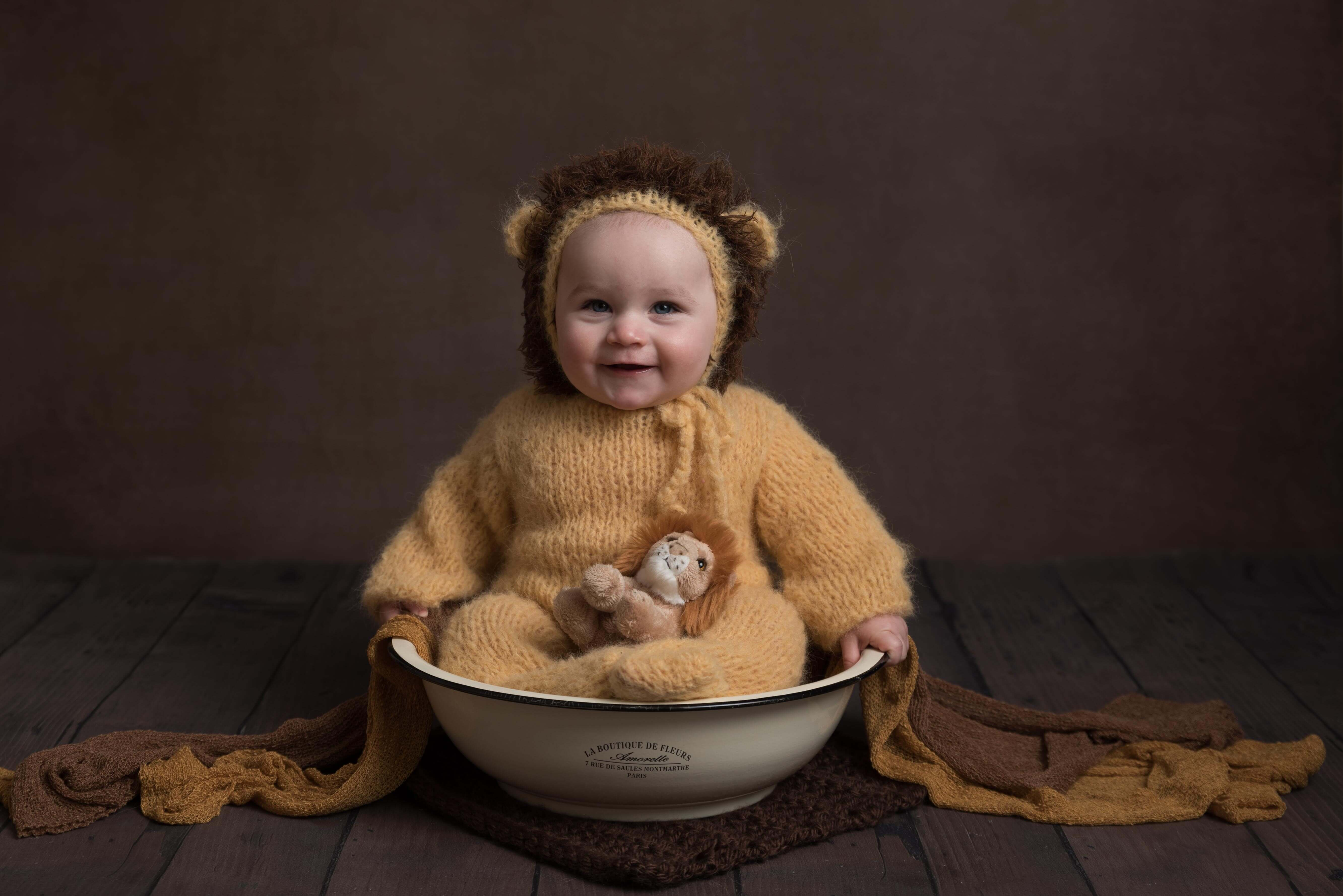 Slice of Life Little Sitters Session Gallery - Baby wearing a lion onesie holding a lion toy