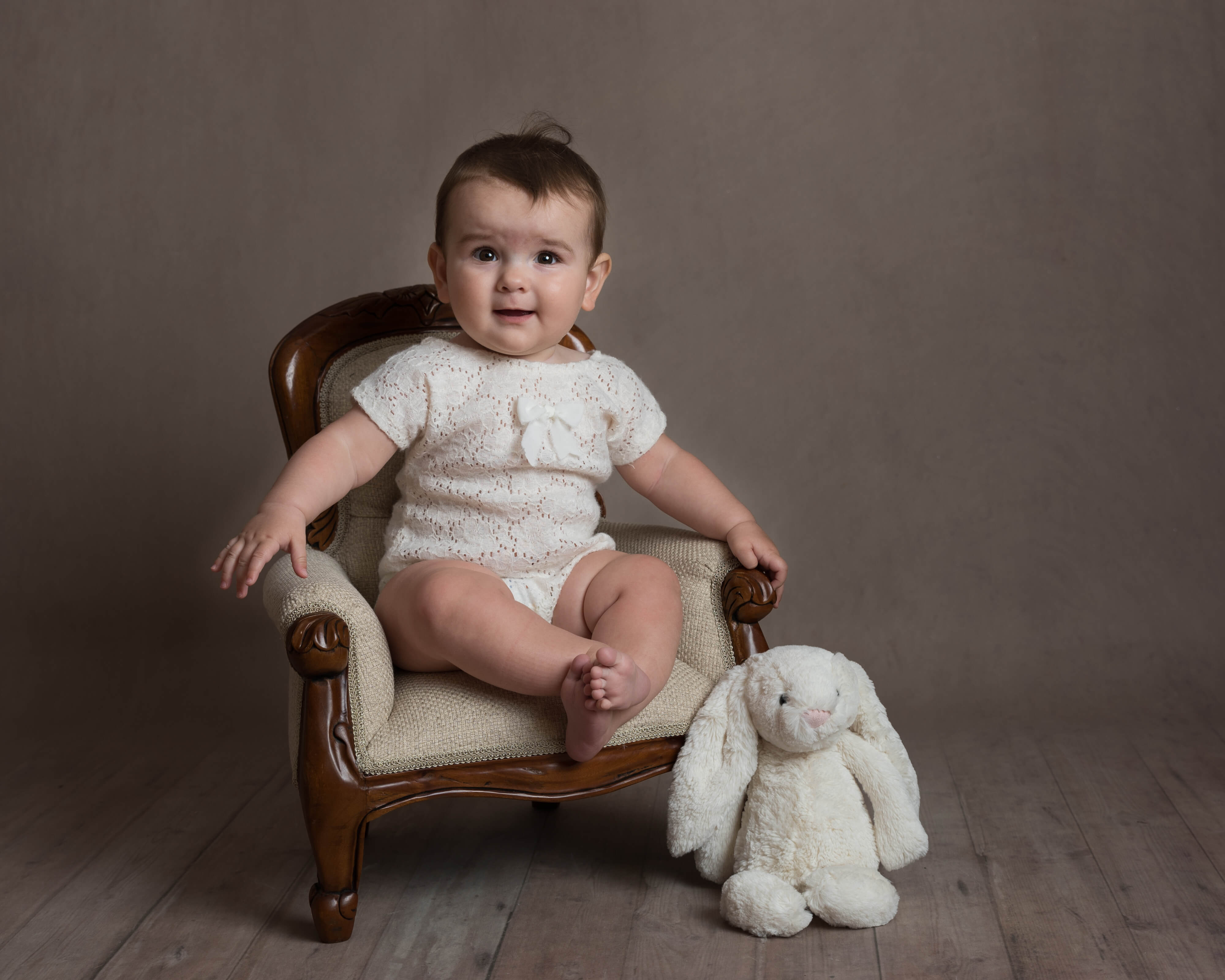Slice of Life Little Sitters Session Gallery - Baby girl sat in a chair posing with a cuddly rabbit toy
