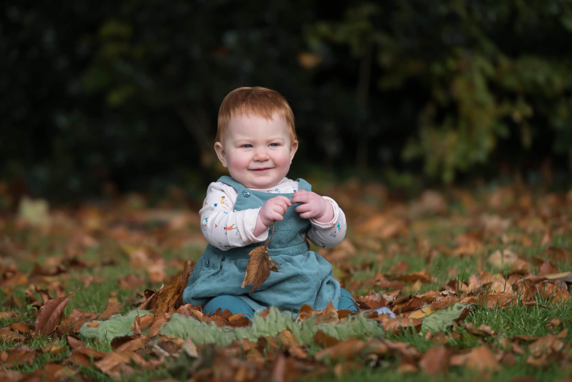 Baby playing with leaves during an outdoor photoshoot - Slice of Life Photography - Spalding photographer