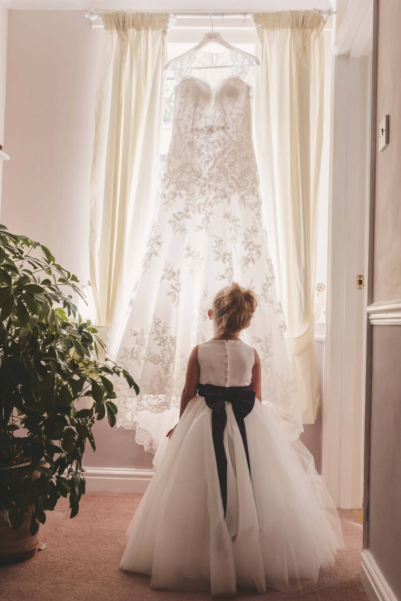 Flower girl admiring wedding dress - Reportage wedding photos by Lincolnshire wedding photographer, Slice of Life Photography