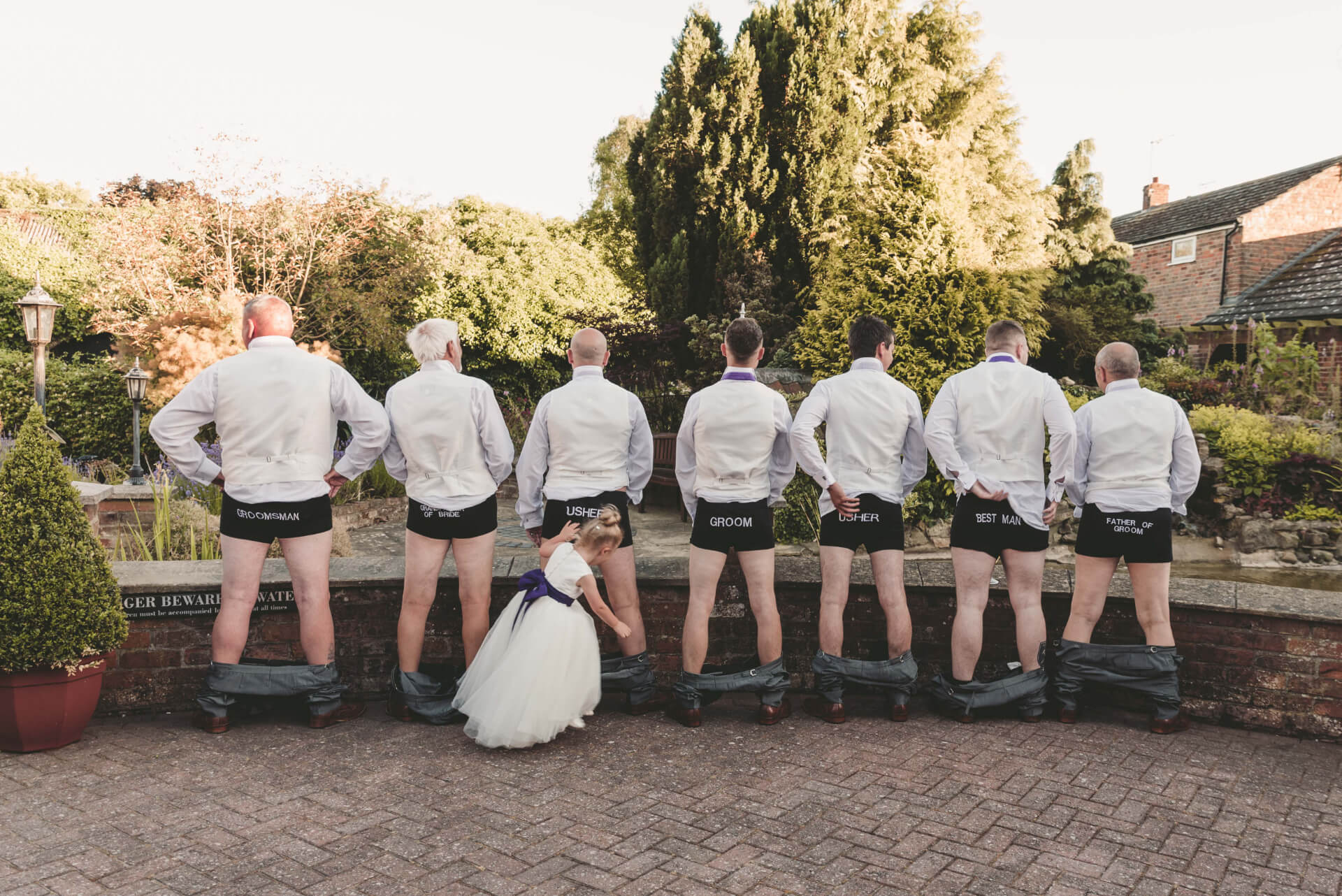 Groomsman flash their named wedding party underwear whilst flower girl looks on at Whaplode Manor wedding reception - photograph by Slice of Life Photography,Lincolnshire wedding photographer