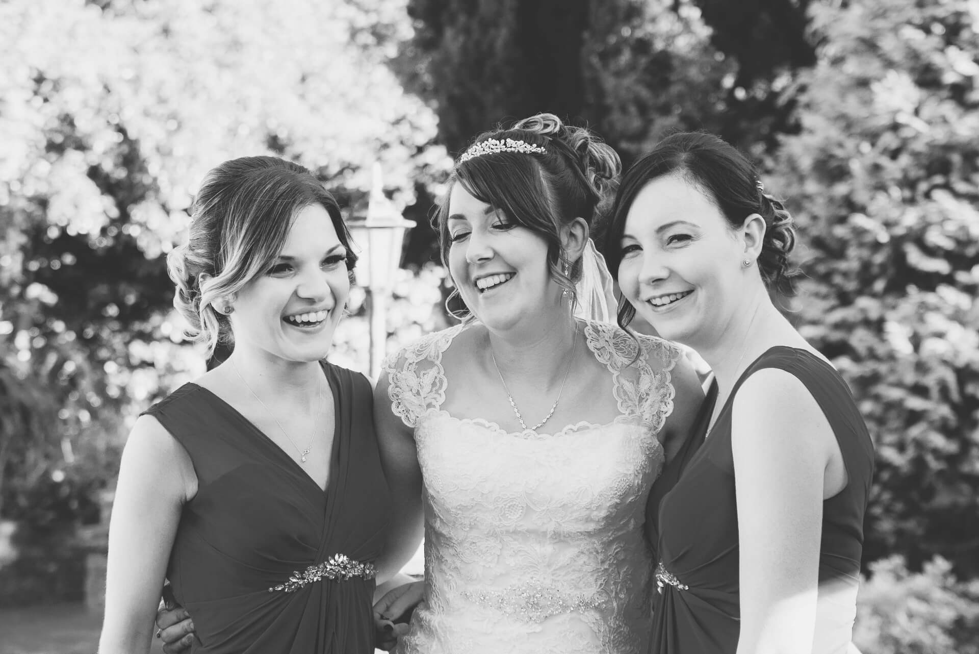 Bride and Bridesmaids laughing at Whaplode Manor Wedding Reception - Black and white wedding photo by Slice of Life Photography, Spalding