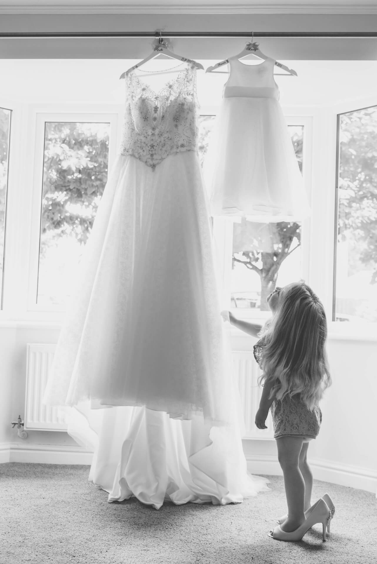 flower girl looking at the wedding dress - natural wedding photography by - Slice of Life Photography