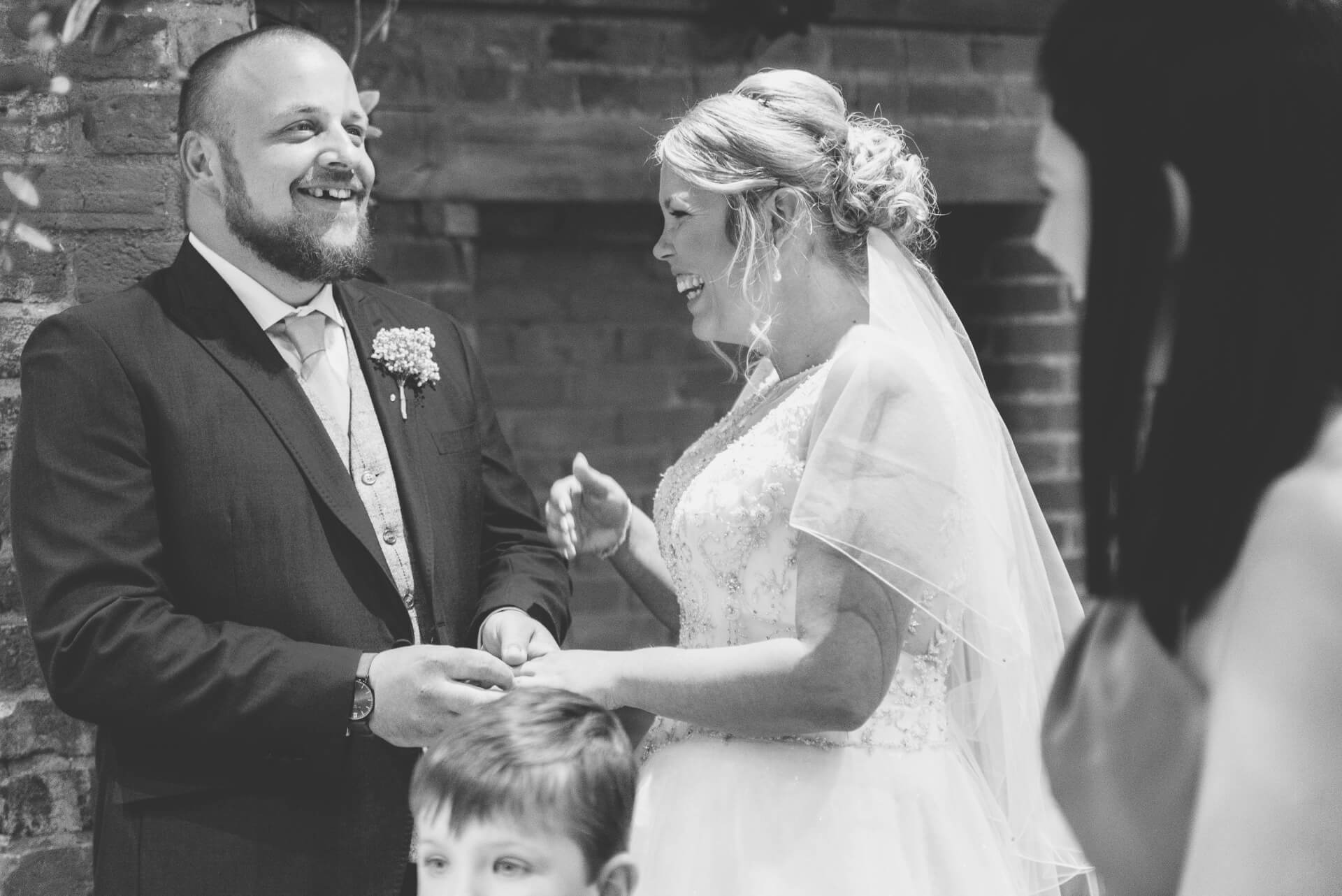 Bride and Groom laughing during wedding ceremony - natural wedding photography at Whaplode Manor by Slice of Life
