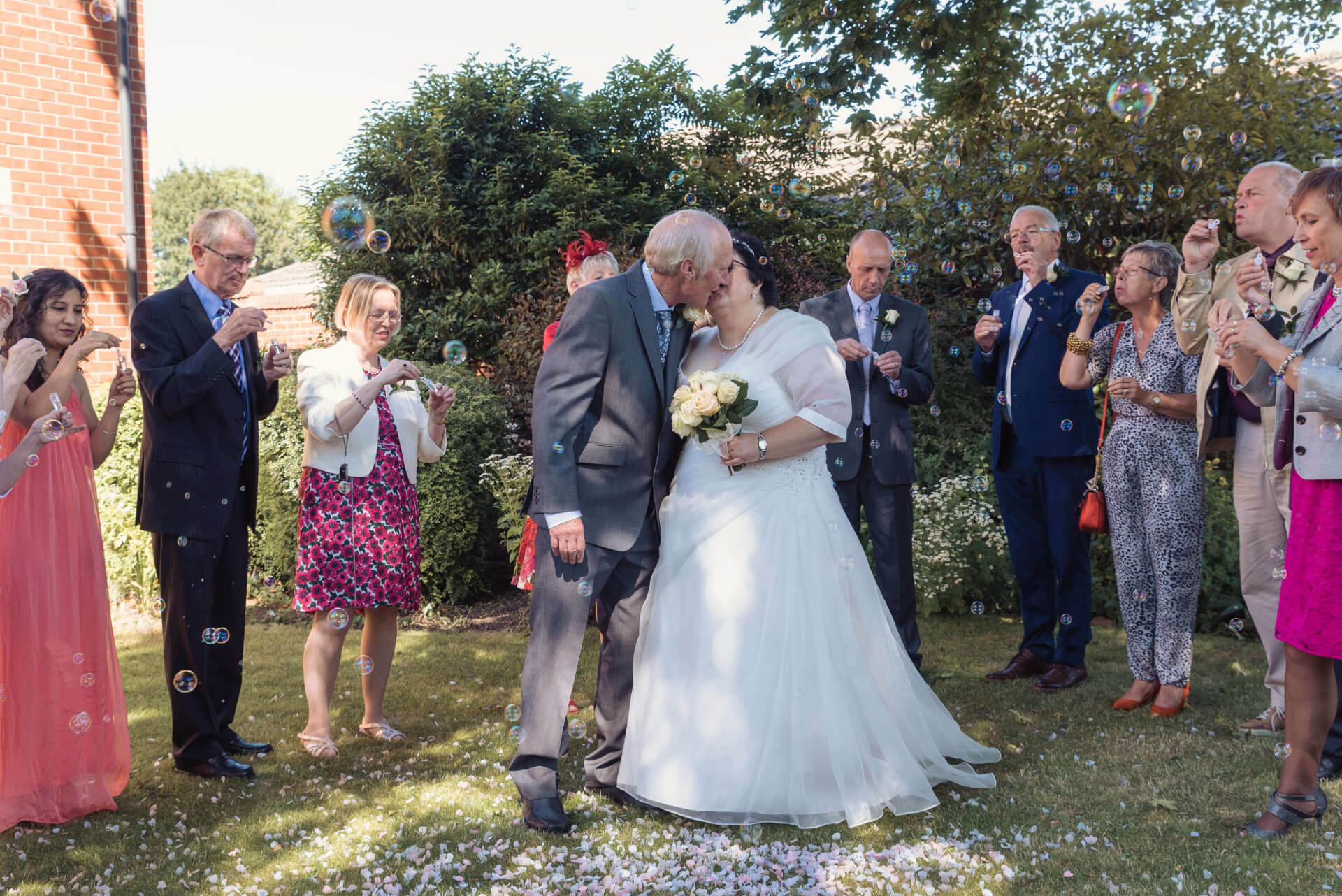 Guests blowing bubbles confetti at Bride and Groom whilst they kiss, at Woodlands Hotel, Spalding - Wedding Photography by Slice of Life