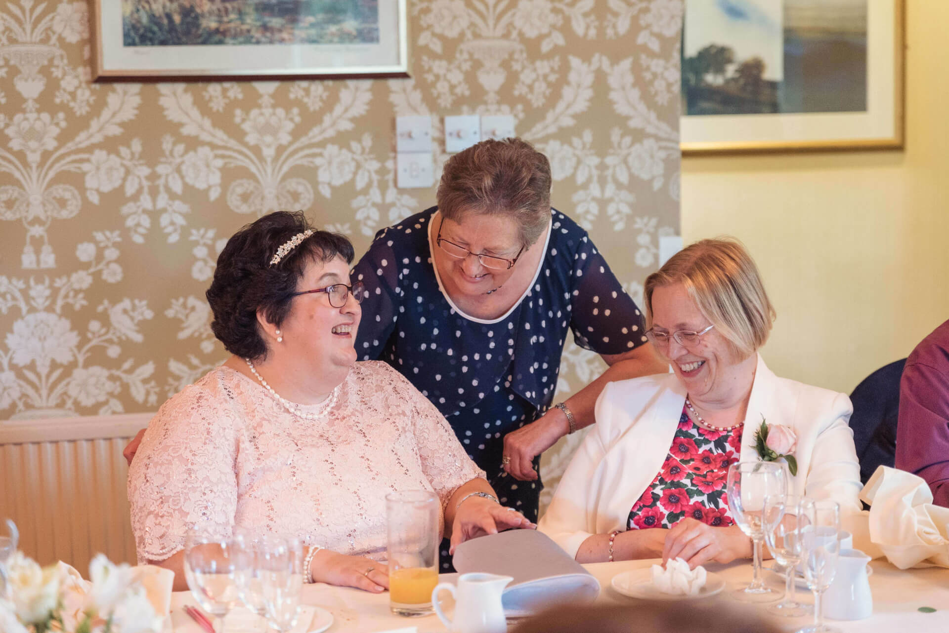 Bride and friends laughing during wedding reception - wedding photography by Slice of Life Photography
