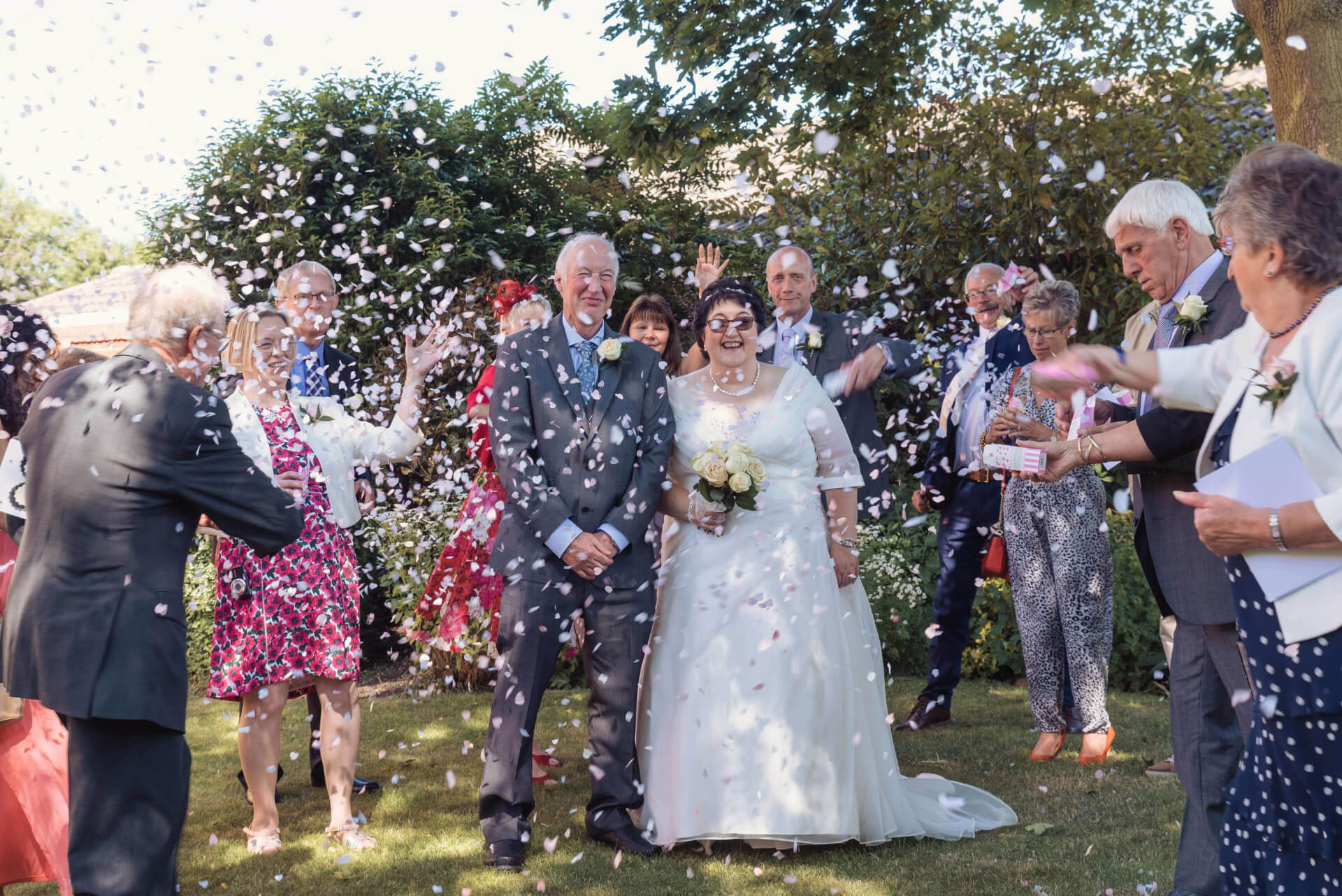 Wedding Guests throwing Confetti at the Bride and Groom at Woodlands Hotel - Wedding Photography by Slice of Life Photography